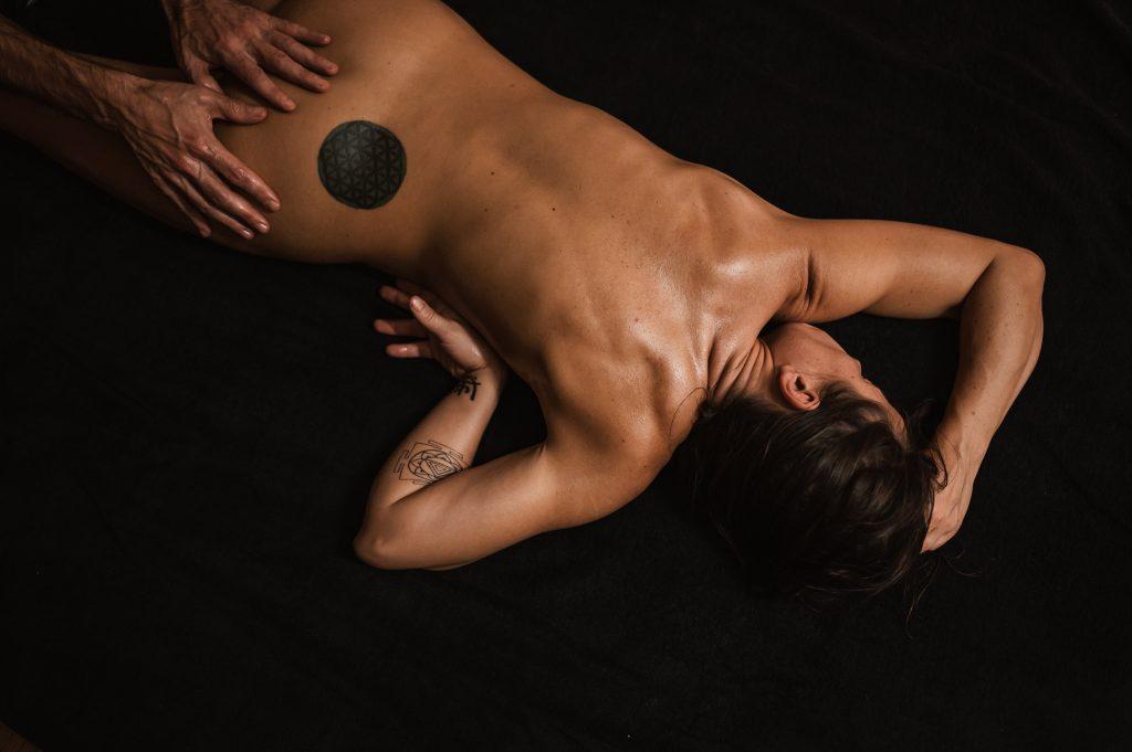 massage naturiste parisfemme seins nus allongée sur du textile noir femme seins nus allongée sur du textile noir